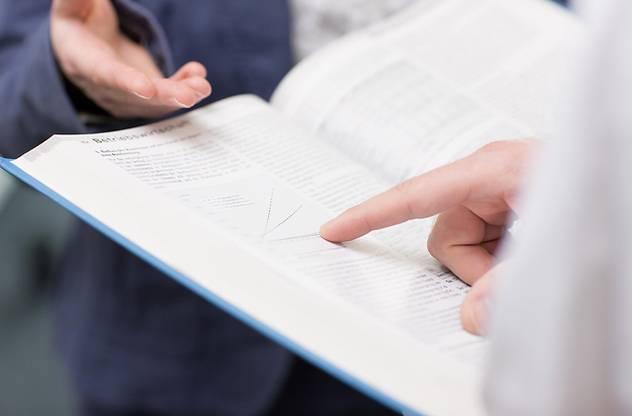 Jemand zeigt auf die Seite eines Buches